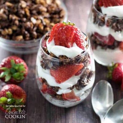 Una foto de parfaits de desayuno con fresas y granola de chocolate negro.