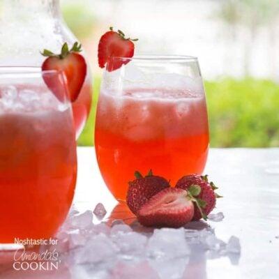 Dos vasos cortos llenos de limonada de fresa servidos con fresas en rodajas en el borde del vaso y al lado.