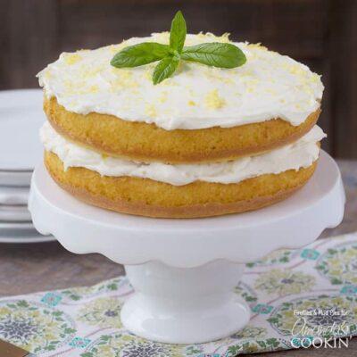 Un primer plano de un poke cake de cuajada de limón sobre un soporte de pastel blanco cubierto con hojas de menta fresca.