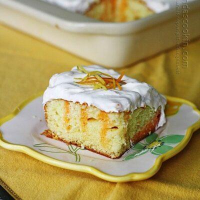 Un trozo de tarta para los amantes de los cítricos en un plato cuadrado.