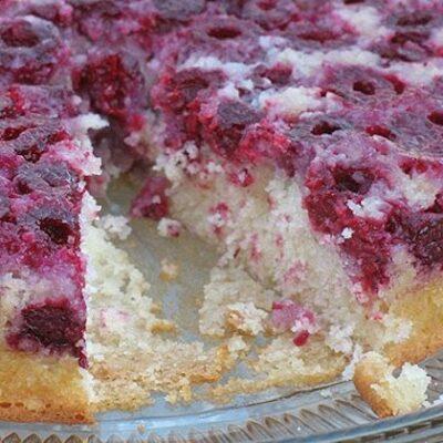 Una foto de un pastel de frambuesa al revés en un plato transparente al que le falta una rebanada.