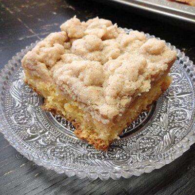 Una foto de un cuadrado de pastel de miga en un plato transparente.