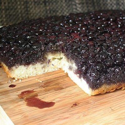 Una foto de un fácil pastel de arándanos boca abajo descansando sobre una tabla de cortar de madera.
