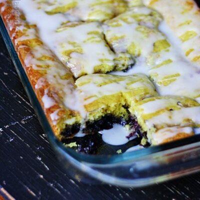 Una foto de tarta de arándanos de limón glaseado en un plato con un trozo eliminado.
