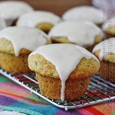 Una foto de muffins de calabacín de atajo descansando sobre una rejilla de enfriamiento cubierta con glaseado de crema agria.