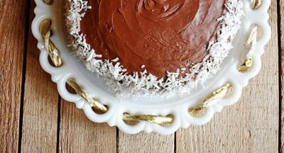 Una fotografía aérea de un pastel de copo de nieve de coco y almendras que descansa sobre un soporte de pastel blanco.