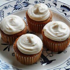 Una foto de cuatro cupcakes de zanahoria de ahorro de tiempo en un plato.