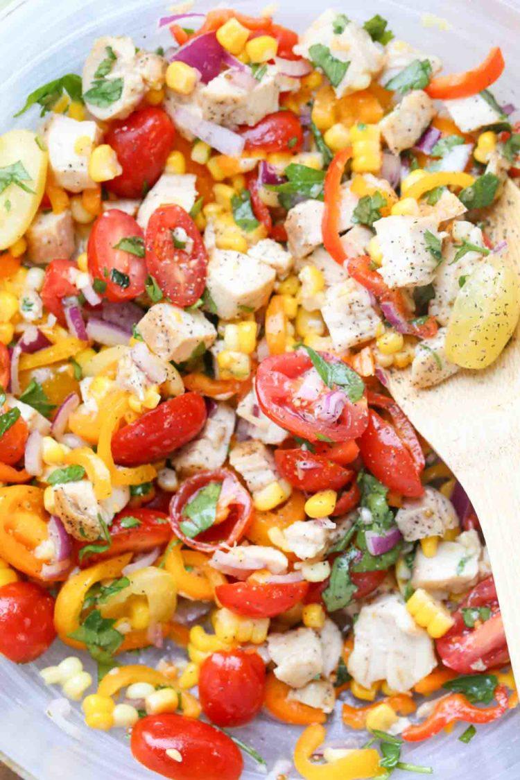 Imagen de cerca de la receta de ensalada de verduras con una cuchara, cubierta con pimienta y verduras.