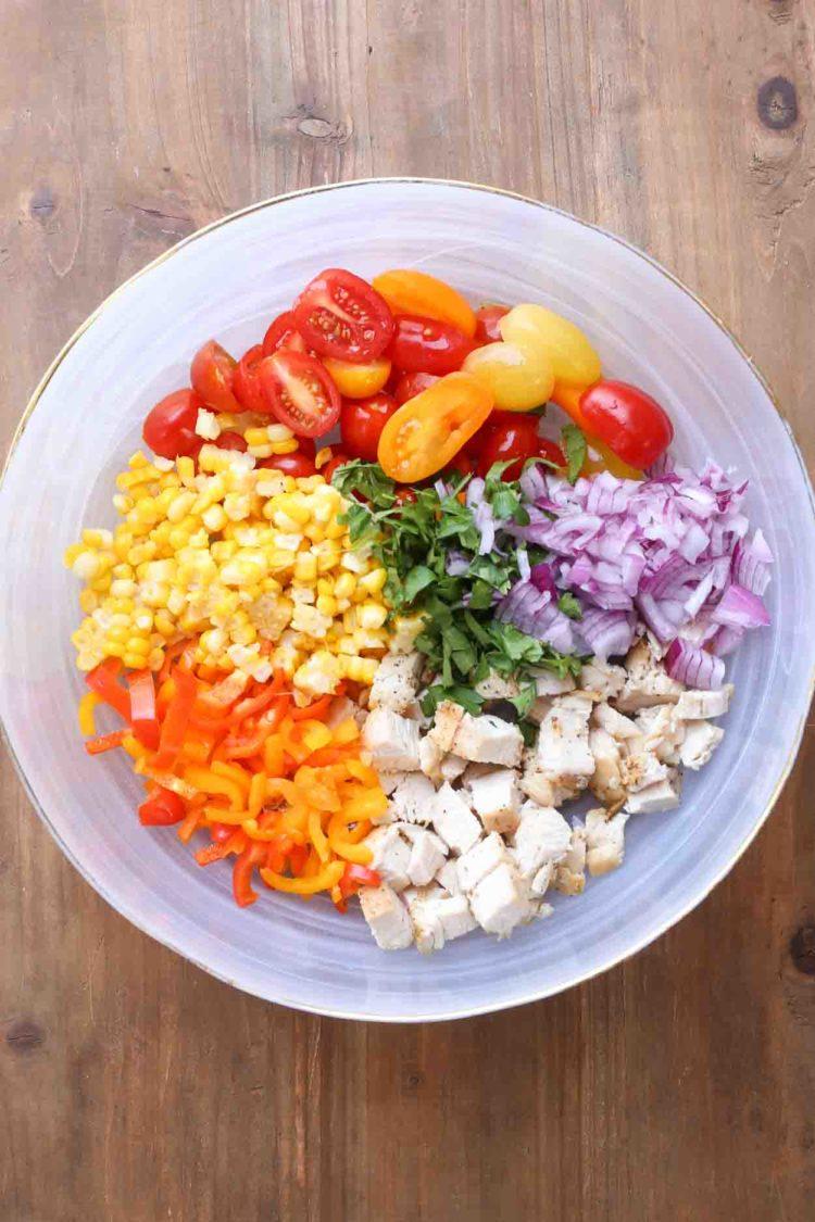 Ensalada de pollo con verduras en un bol con todos los ingredientes.