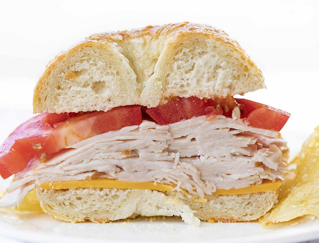 Close Up of the Inside of a Salt Bagel Sandwich with layers of turkey, tomato, and cheese next to chips