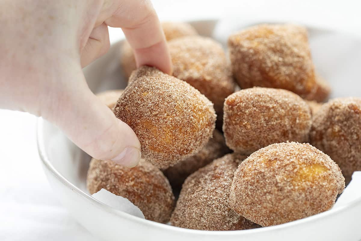 Hand Picking up a Cinnamon Sugar Mini Donut