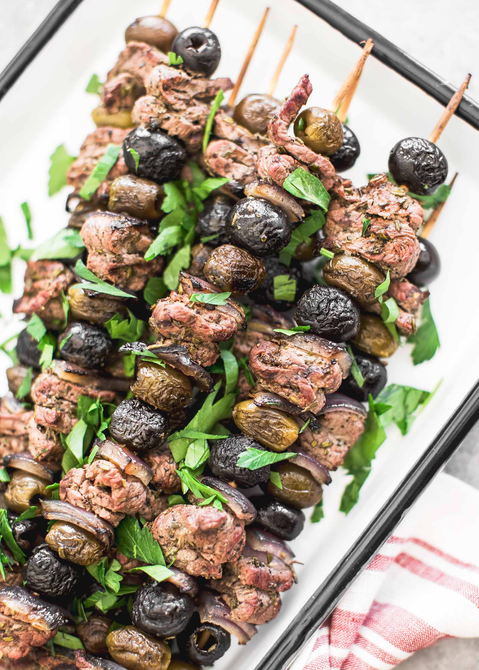 Grilled Steak Kabobs with olives and rosemary on a platter