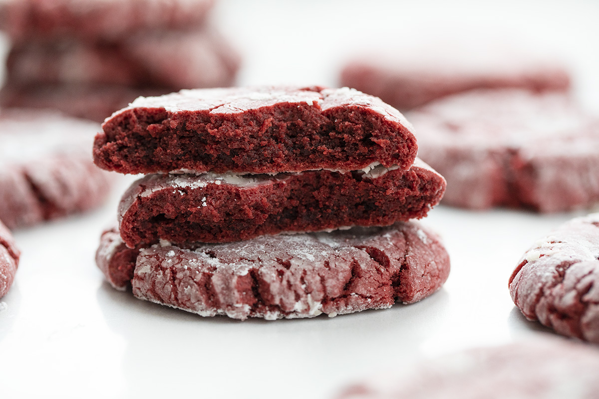 Stacked Red Velvet Peanut Butter Crinkle Cookies with One Broken in Half Showing Inside