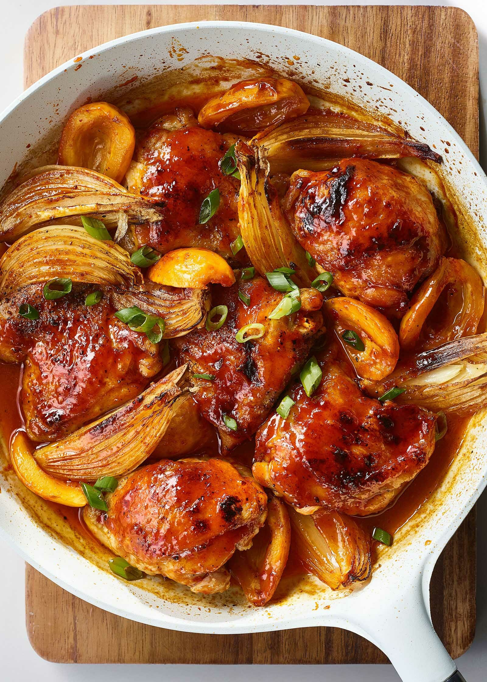 A white skillet with braised chicken thighs, onons and apricots.