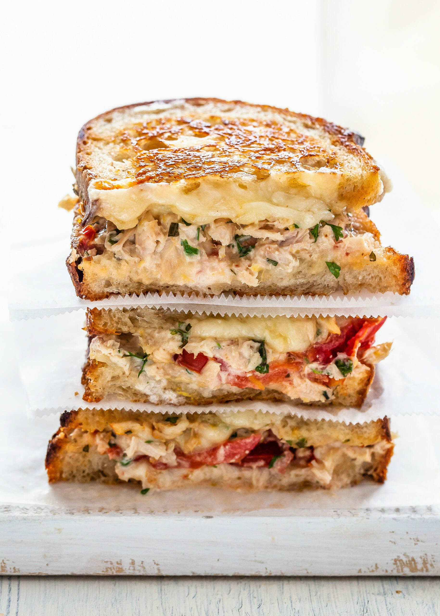 Tuna melt sandwich cut in half and stacked on top of each other. The bread is toasted and tuna, melted cheese and tomatoes are visible in the filling.