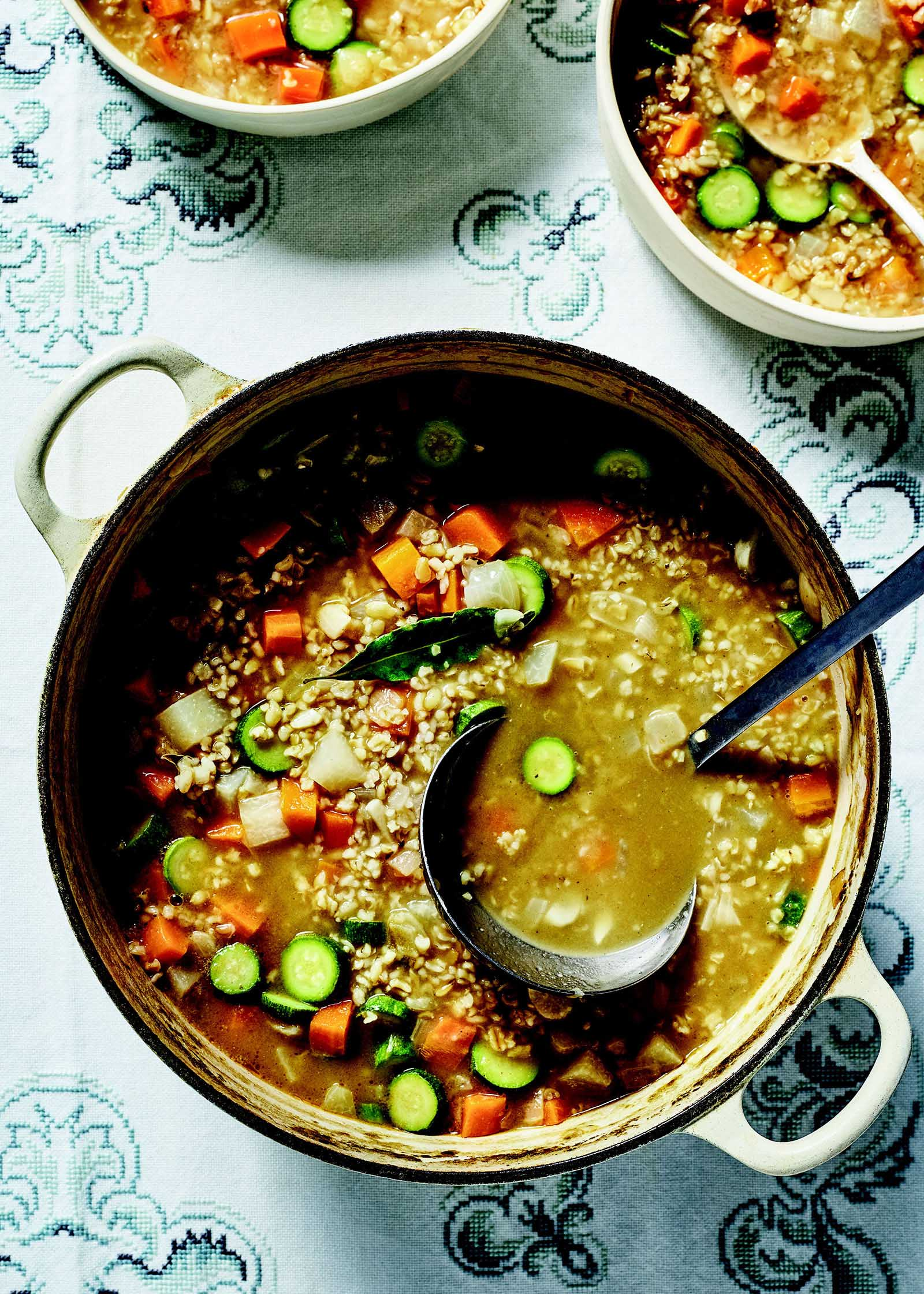 Vegetarian Soup with Freekeh in a dutch oven with a ladle. Two bowls of the soup are in partial view above.